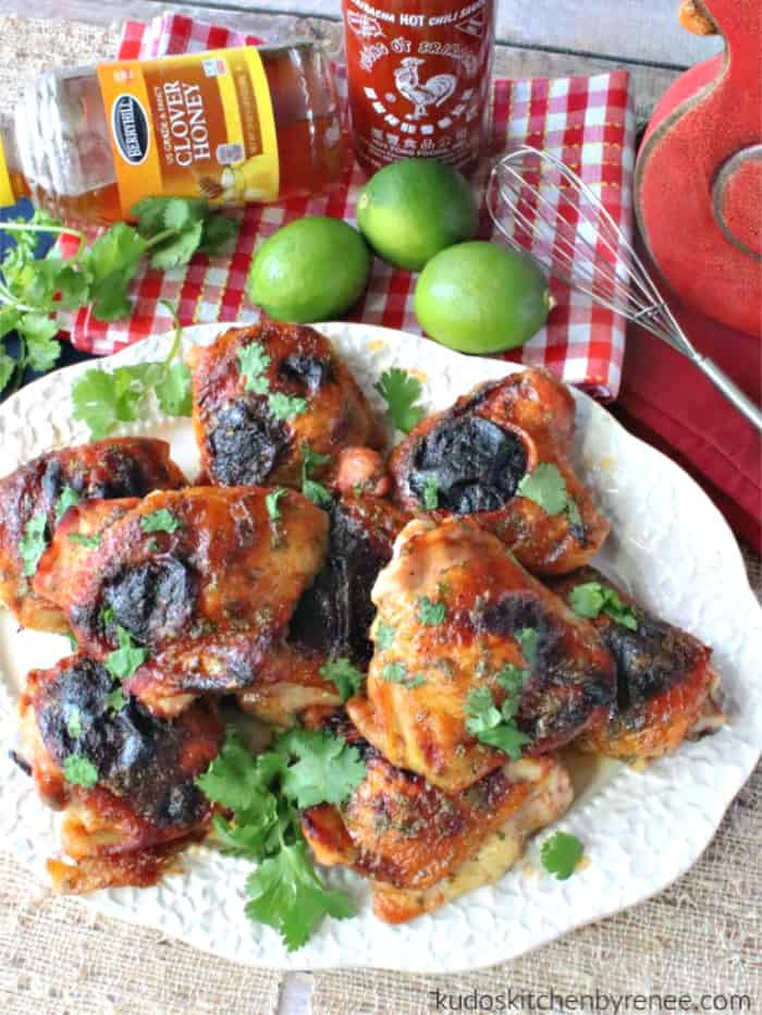 An overhead vertical photo of honey lime sriracha chicken on a platter with a jar or honey, sriracha, limes, and a whisk in the background.