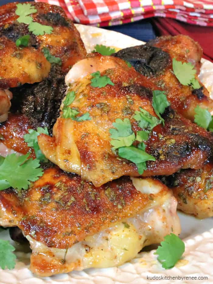 A vertical closeup image of golden brown and succulent chicken thighs with honey lime sriracha sauce piled on a plate with fresh cilantro.