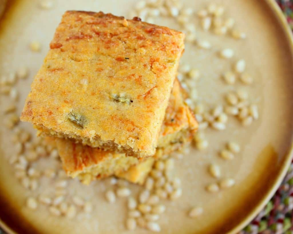 A horizontal overhead photo of a stack of Jalapeno cheddar cornbread on a golden color plate with corn kernels on the plate.
