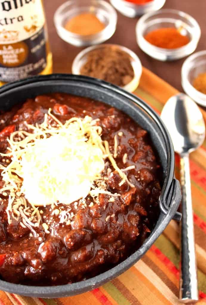A vertical closeup image of a bowl or turkey mole chili with a spoon on the side and a bottle of beer in the background.