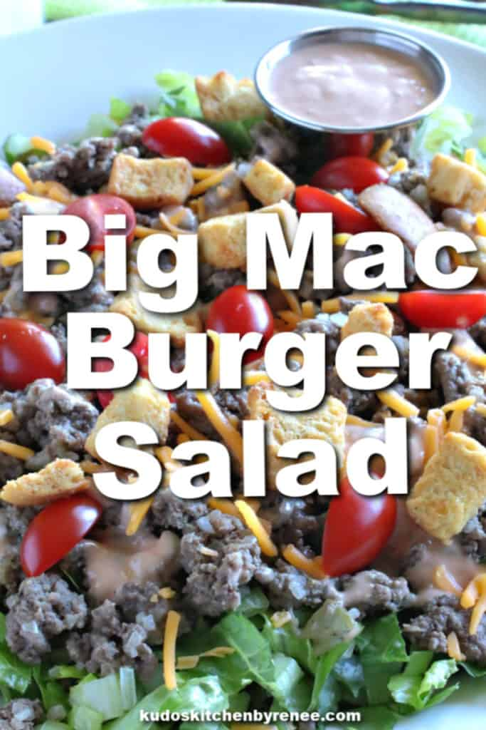 A closeup vertical image of a big mac cheeseburger salad with croutons, ground beef, tomatoes, and special sauce.