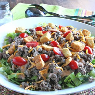 A huge big mac salad in a white bowl with tongs in the background.