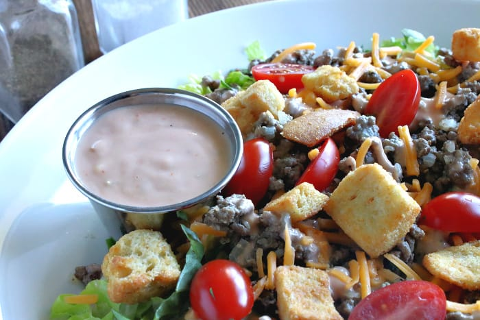 A very close horizontal photo of special sauce on the side of a big bowlful of big mac cheeseburger salad with croutons, cheese, and ground beef.