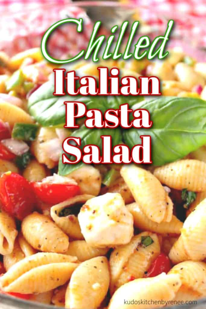Closeup photo of a chilled Italian pasta salad with basil and tomatoes with a title text overlay graphic