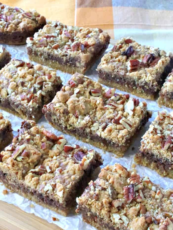 A vertical photo of lined up Nutella cookie bars on a board with crunched up parchment paper.