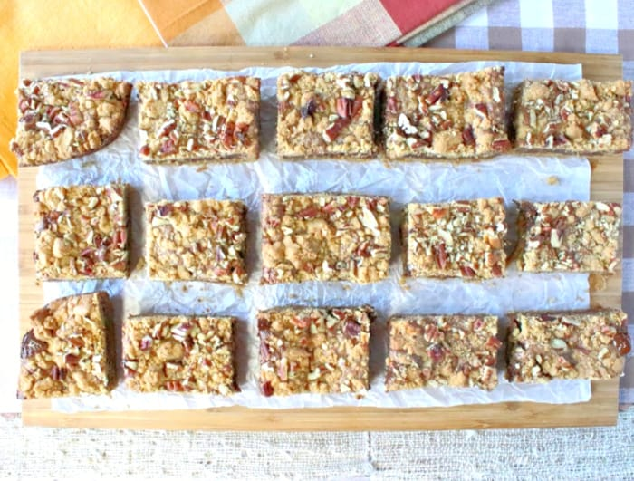 An overhead horizontal photo of Nutella cookie bars on a wooden board with chopped pecans and parchment paper.