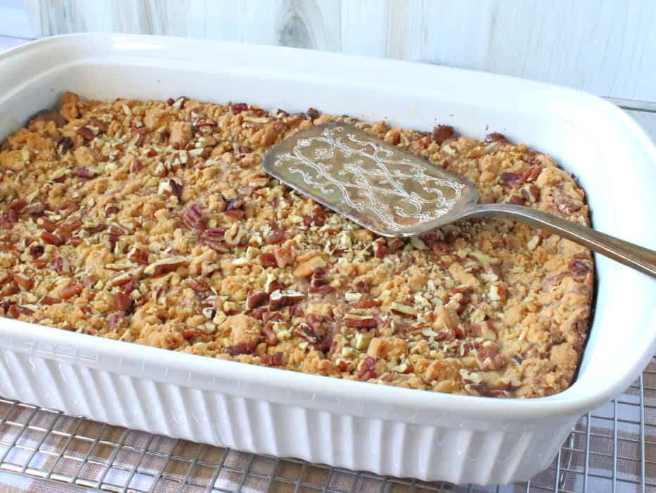A horizontal photo os a 9x13 pan filled with hazelnut spread cookie bars with a serving utensil on the top.