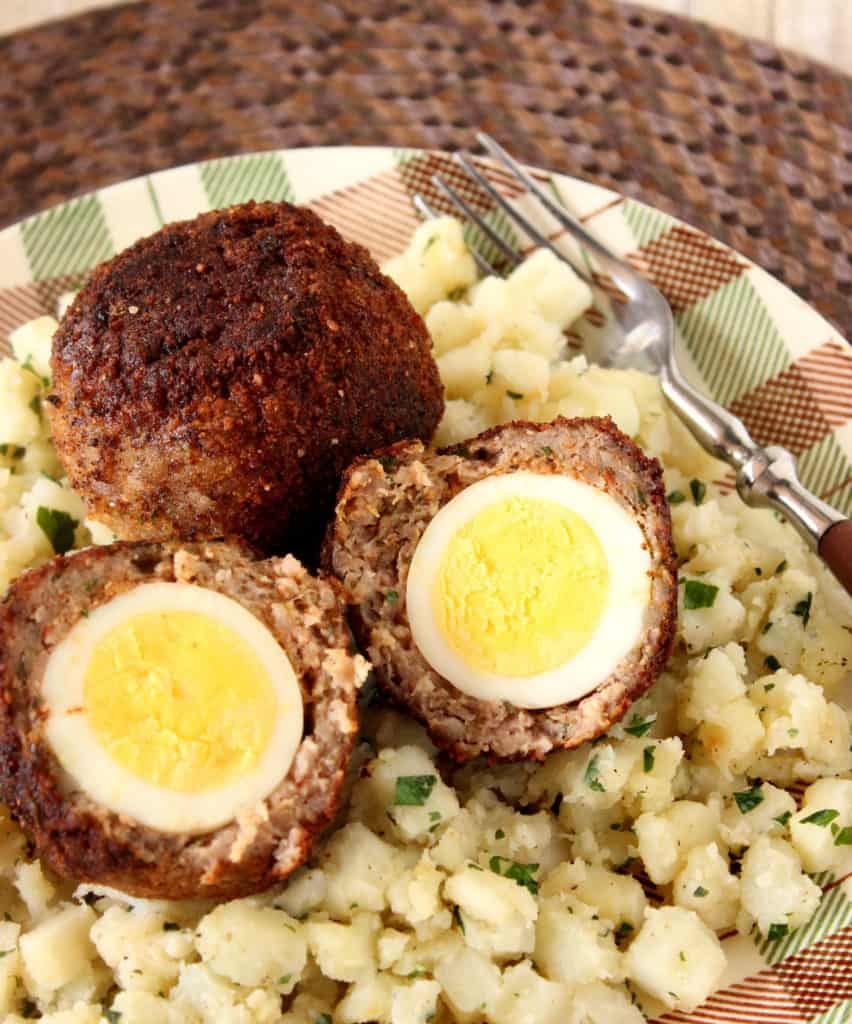 A vertical overhead closeup image of two Scotch eggs on a plaid plate along with some hash brown potatoes and a fork.