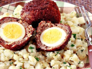 A closeup horizontal photo of two Scotch Eggs on a plaid plate with potatoes and a fork.