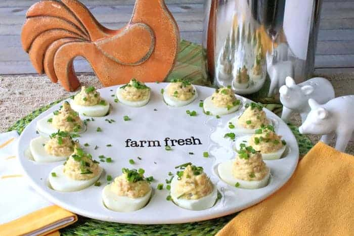 A decorative plate filled with deviled ham and eggs with chives as garnish