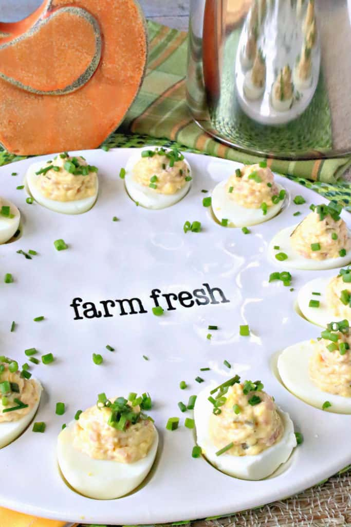 A vertical closeup image of deviled eggs on a white farm fresh plate with chopped chives as garnish. Deviled Dijon Ham and Eggs