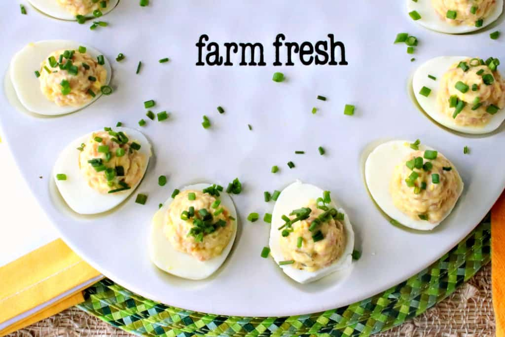 An overhead horizontal photo of a platter of deviled Dijon eggs with ham and chives as garnish on a green place mat with yellow accents.