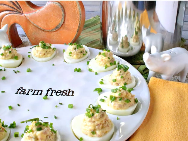 An offset horizontal photo of deviled Dijon eggs with ham and chives on a cute white plate with a sauce pot and a pig salt shaker in the background.
