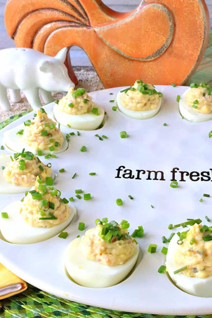 A closeup vertical photo of a tray of deviled Dijon eggs with ham, chopped chives and a ceramic pig salt shaker in the background.