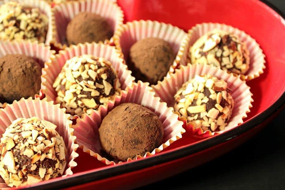 A horizontal closeup photo of Mexican candy truffles in paper cups in a red bowl for valentines day.