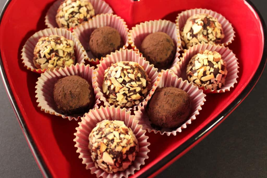 A vibrant horizontal photo of chocolate truffles covered in nuts and coco powder in a red heart shaped dish with paper cups.