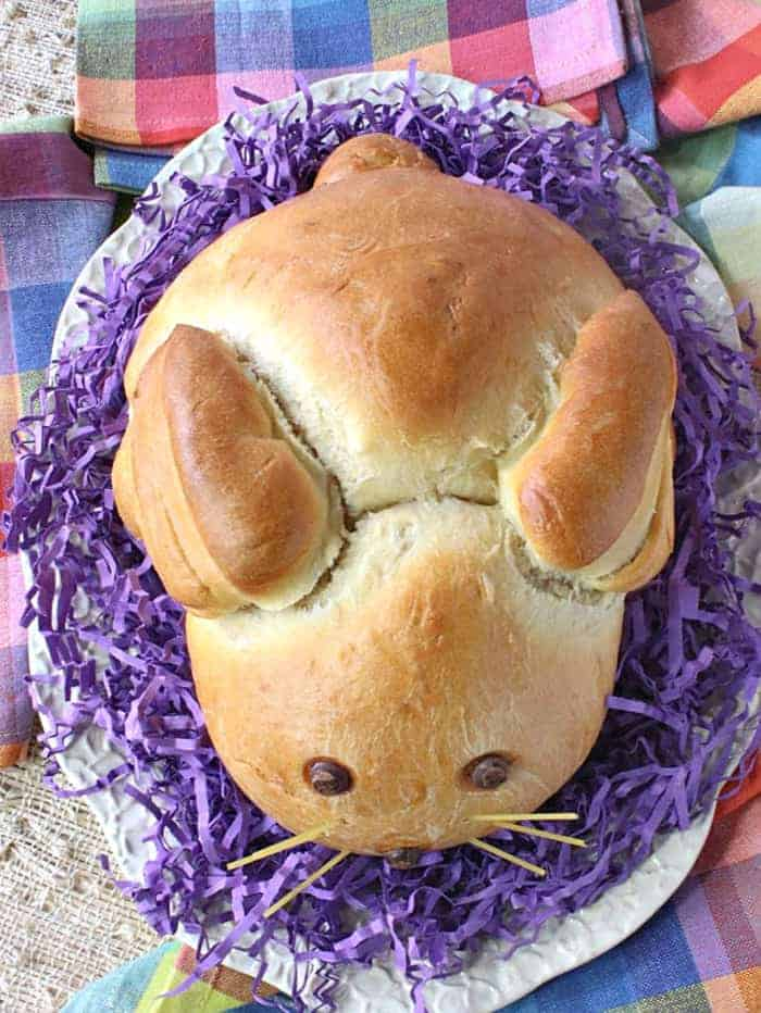 An overhead photo of a loaf of shaped Easter Bunny Bread on a white oval platter with purple Easter grass.