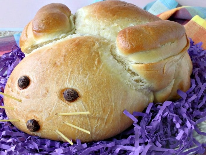 A Easter bunny bread on a white platter with purple Easter grass and colorful napkins.