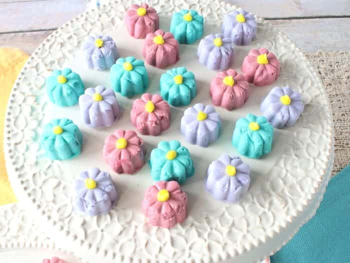 An overhead photo of colorful butter mint flower candy on a pretty cake stand.