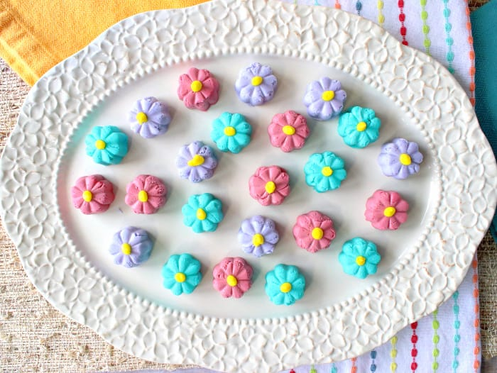 A horizontal overhead photo of a decorative oval platter filled with colorful butter mint candy flowers in pink, purple, and aqua.