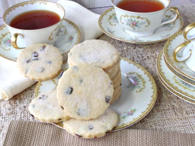 A stack of orange cardamom cookies on a china plate with tea cups in the background.