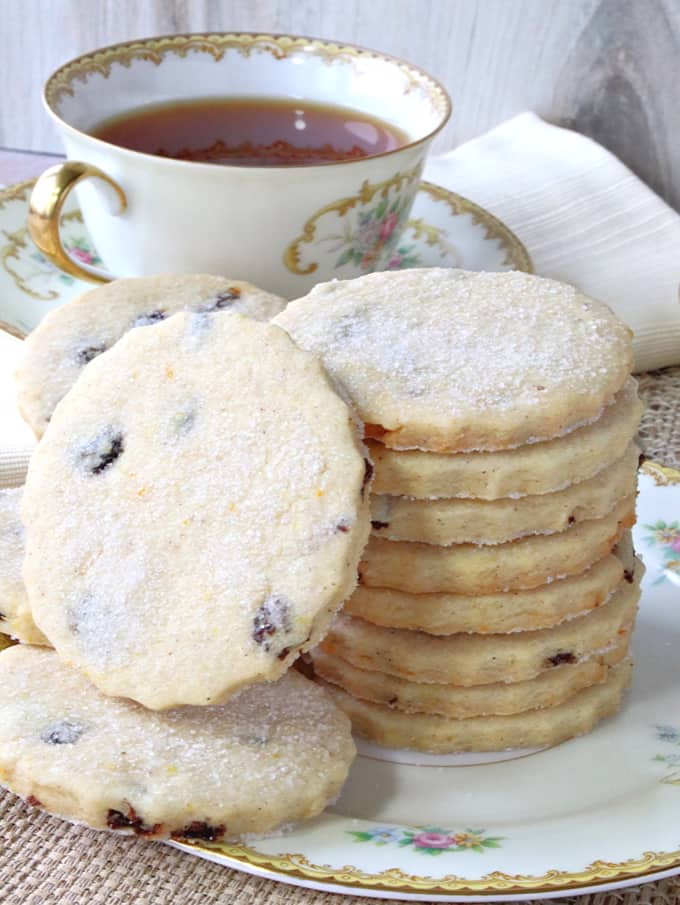 A closeup vertical picture of orange cardamom biscuits with sugar coating and currants.