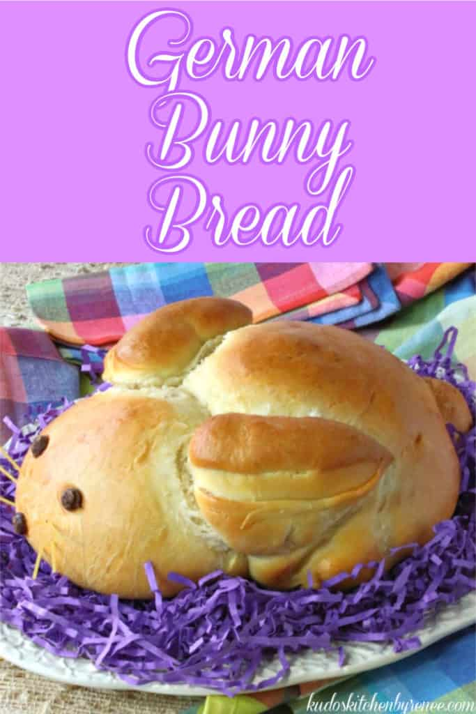 A vertical closeup photo of German bunny bread sitting on purple Easter grass with colorful text.