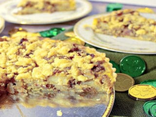 An Irish Cheese and Potato Tart in the foreground with slices on china plates in the background.