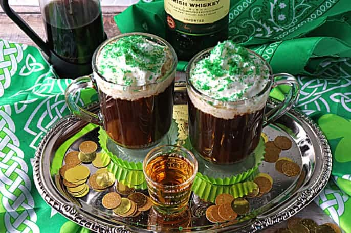 Fun photo of two mugs of Irish coffee on a silver tray with a shot glass of Irish whiskey, green napkins, and faux gold coins.