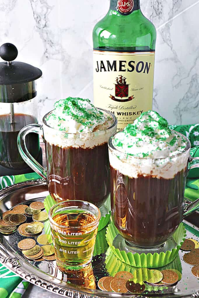 A vertical closeup of two mugs of Traditional Irish Coffee on a silver platter with gold coins and a shot of whiskey in the front.