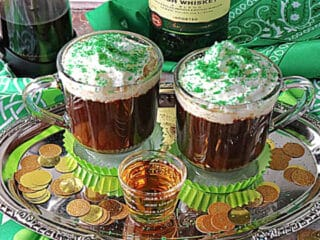 Two mugs of Traditional Irish Coffee on a silver tray with a shot of whiskey in the center.