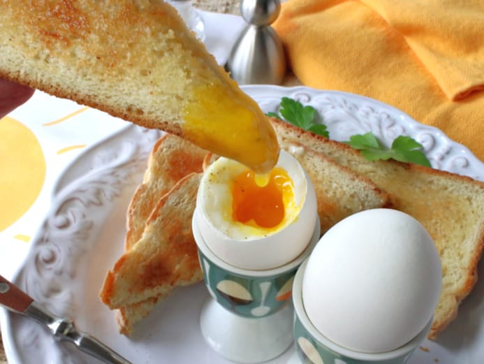 A toast point being dipped into a runny yolk of a soft boiled eggs.