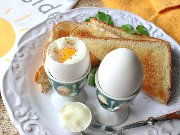 Two soft boiled eggs cooked in a air fryer in eggs cups with toast on a white plate