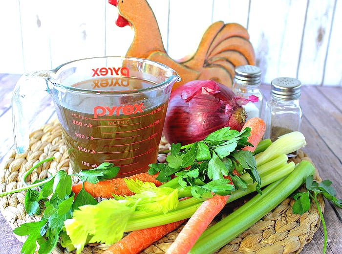 A glass measuring cup filled with budget-friendly and healthy homemade chicken stock with carrots, celery, parsley on a woven rattan place mat.