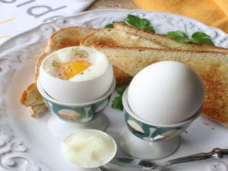 Two air fryer soft boiled eggs in egg cups with toast on a white plate with parsley and a spoon.