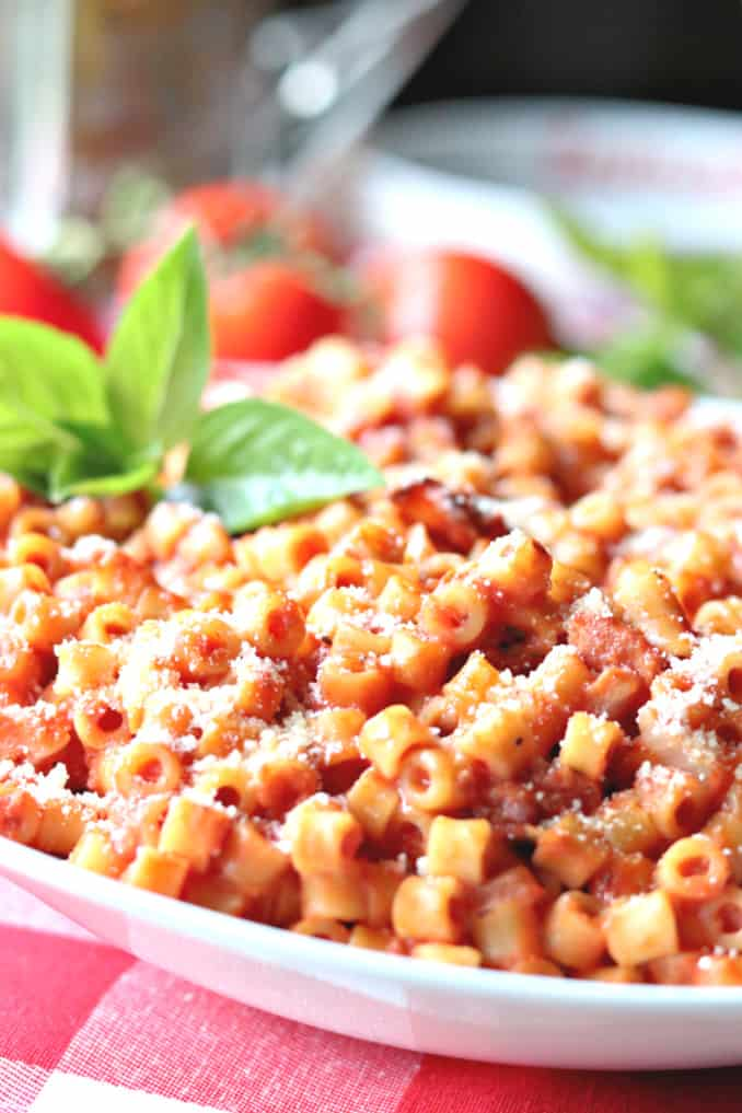 A vertical closeup image of tomato bacon pasta in a white bowl with fresh basil as garnish.