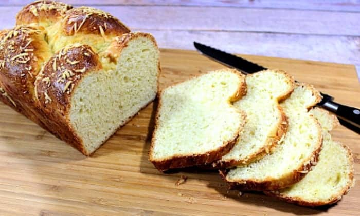 A sliced loaf of Italian cheese bread on a bread board with a serrated knife.