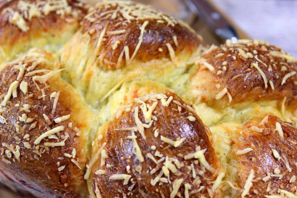 Closeup photo of a golden brown loaf of braided Italian Easter cheese bread.
