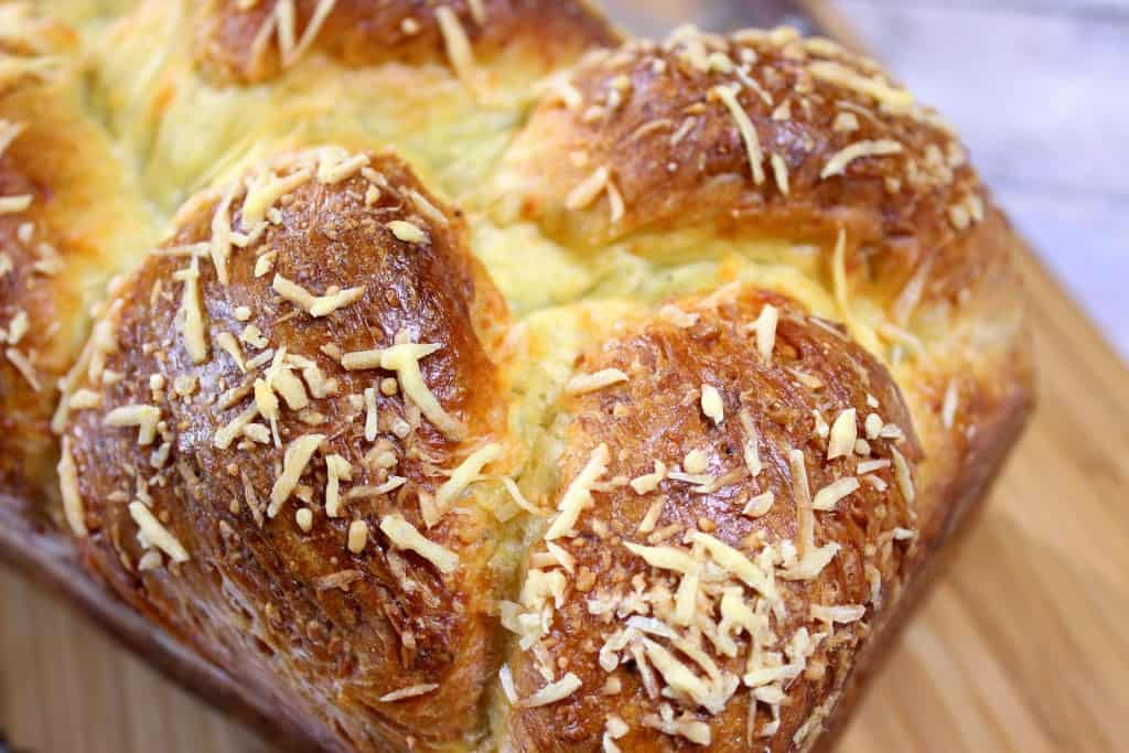 Closeup horizontal photo of a golden loaf of Italian Easter cheese bread with sprinkled shredded cheese.