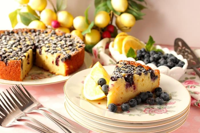 A slice of lemon ricotta cake on a plate with the whole cake in the background with lemons and blueberries as garnish.