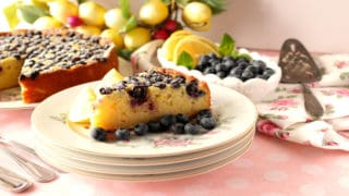 A slice of lemon ricotta cake on pretty plates with a whole cake in the background along with fresh blueberries and lemons