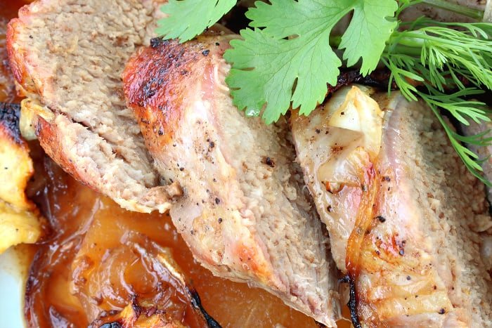 Closeup photo of thick slices of pineapple pork tenderloin with fresh cilantro.