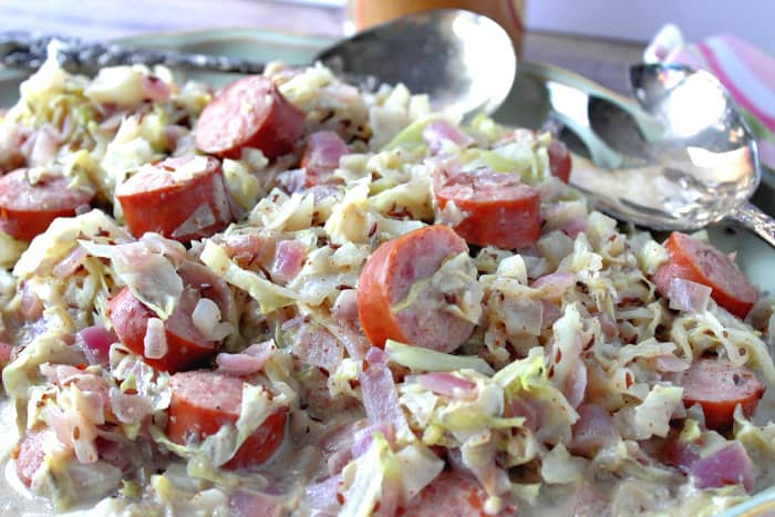 Closeup horizontal photo of creamed cabbage with caraway and sausage with silver serving utensils in the background.