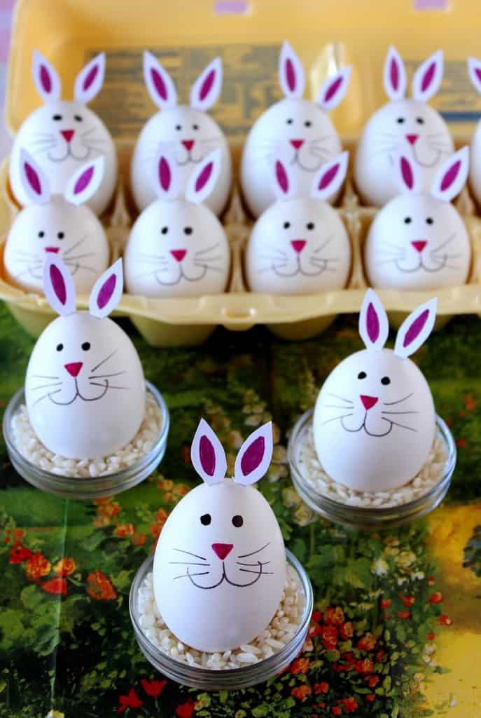 Vertical photo of a bunch of hard-boiled bunny eggs with pink noses, whiskers, and cute bunny ears.