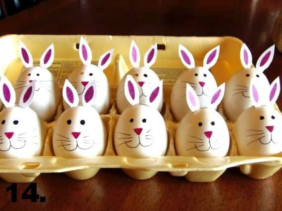 An egg carton filled with hard-boiled bunny eggs with pink noses, whiskers, and bunny ears.