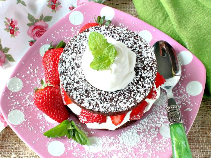 Overhead photo of a round brownie filled with whipped cream and strawberries on a pink polka dot plate.