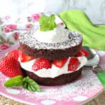A colorful photo of a brownie strawberry shortcake on a pink polka dot plate with fresh strawberries and mint.