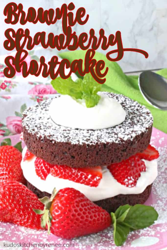 A closeup vertical image of a brownie strawberry shortcake with whipped cream, fresh strawberries and mint leaves.