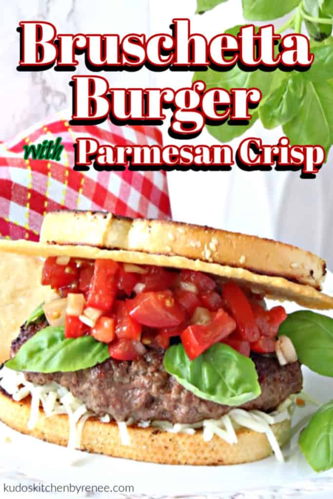 Closeup vertical image of a bruschetta burger with a Parmesan cheese crisp, fresh tomato relish, and basil leaves.