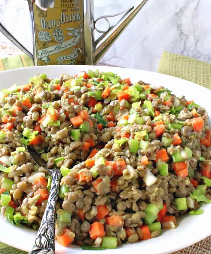 A closeup photo of a chilled lentil salad with carrots, celery and a serving spoon.